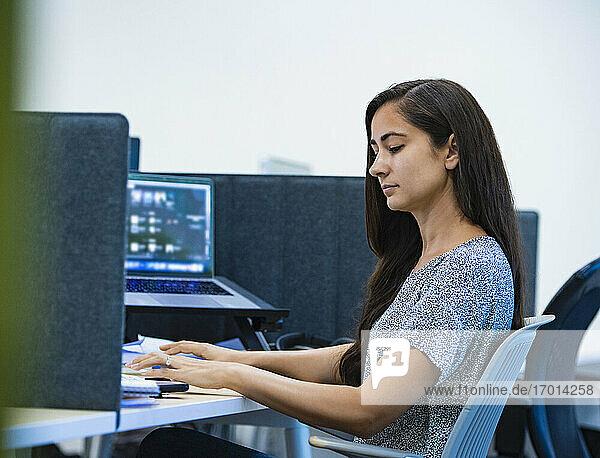 Frau mit Computer am Schreibtisch im Büro