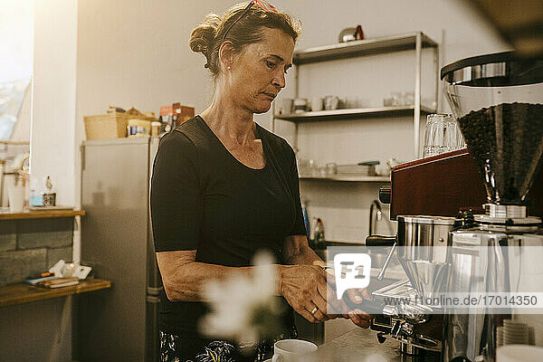 Senior female owner making coffee in cafe