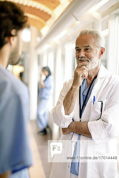 Male nurse talking to smiling wrinkled expert in hospital