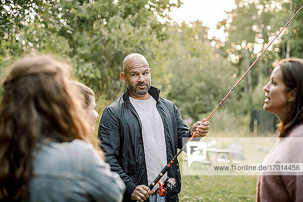 Father with fishing rod talking to daughters while standing by partner in yard