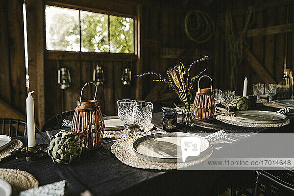 Plates and glasses arranged on dining table during social gathering
