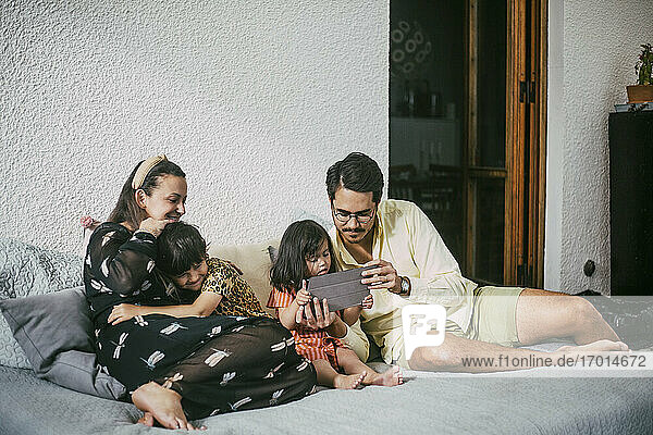 Father and disabled daughter using digital tablet while smiling girl embracing mother on sofa at home