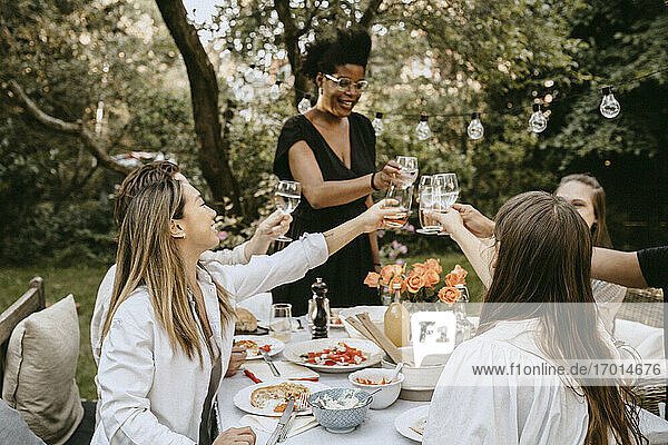 Smiling woman toasting drinks with friends over table during social gathering