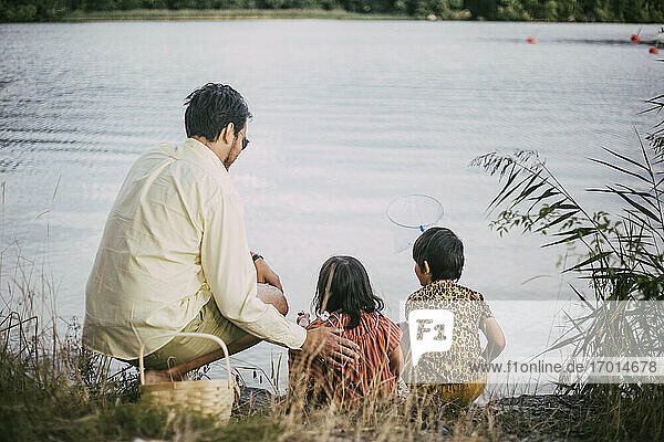 Rear view of father with down syndrome daughter fishing by lake