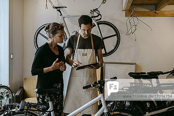 Male owner with digital tablet by senior customer in bicycle workshop