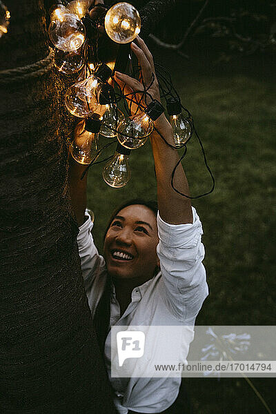 Smiling female hanging lighting equipment on tree trunk in yard during dinner party