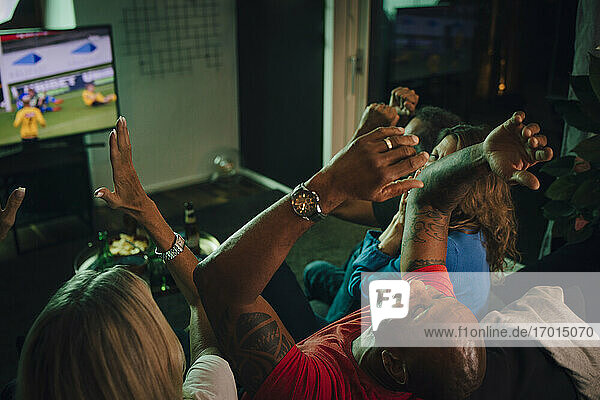High angle view of friends cheering while watching sports on TV in living room