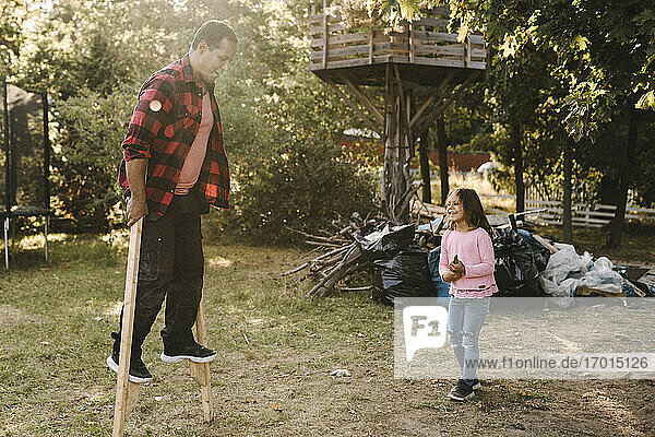 Happy children looking at father balance on wooden sticks in backyard