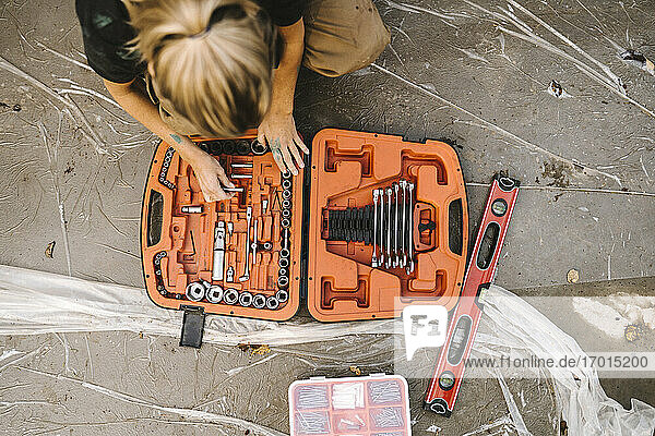 High angle view of woman with toolbox over concrete land