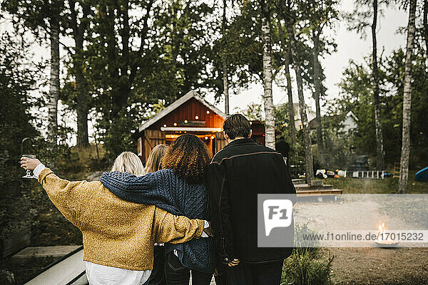 Rear view of women with man walking against cottage during social gathering