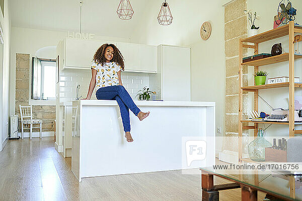Smiling young afro woman sitting on kitchen counter at home