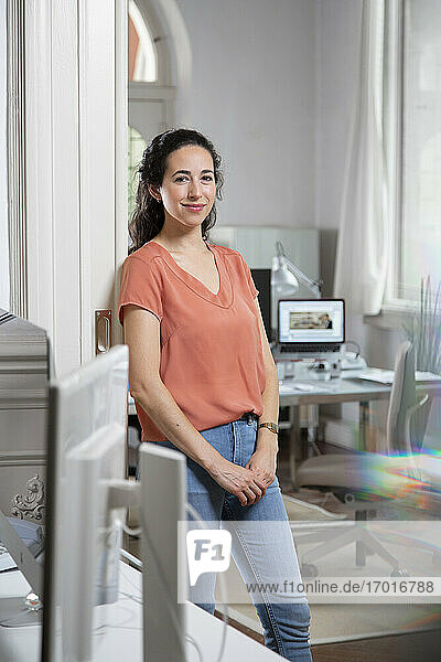 Smiling businesswoman leaning on doorway in office