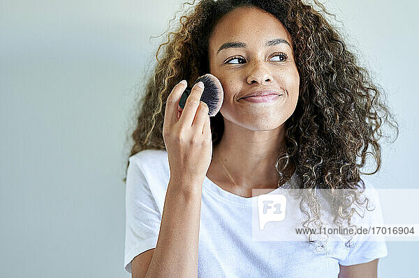 Smiling young woman applying face powder with make-up brush against white wall