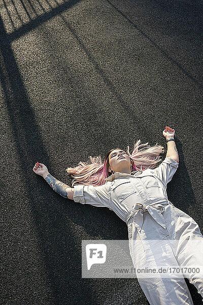 Rosahaarige junge Frau mit erhobenen Armen  die auf einem Platz liegt Rosahaarige junge Frau mit erhobenen Armen, die auf einem Platz liegt