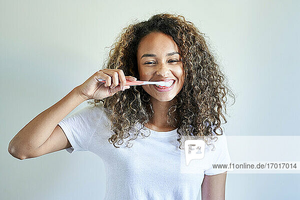 Happy young woman enjoying while brushing teeth against wall