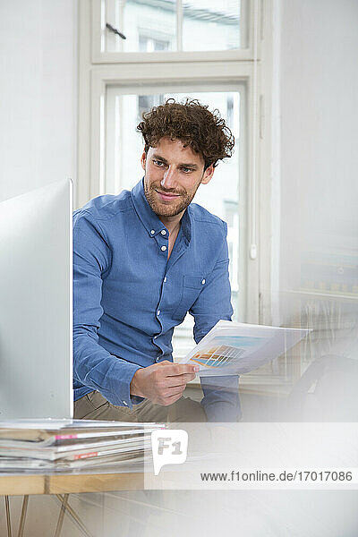 Young businessman with document using computer while working at office
