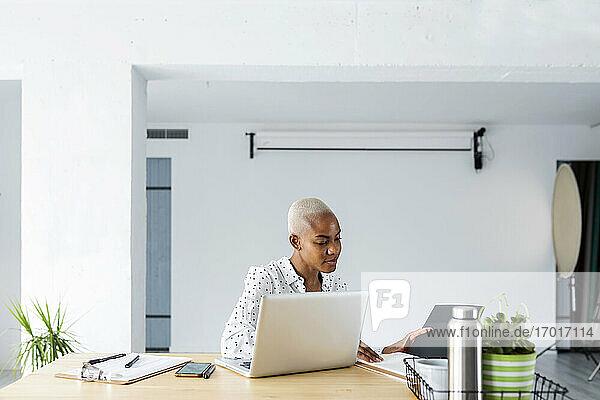 Kurzhaarige Frau arbeitet in einem hellen  modernen Büro Kurzhaarige Frau arbeitet in einem hellen, modernen Büro