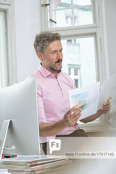 Mature businessman reading document by computer at office cabin