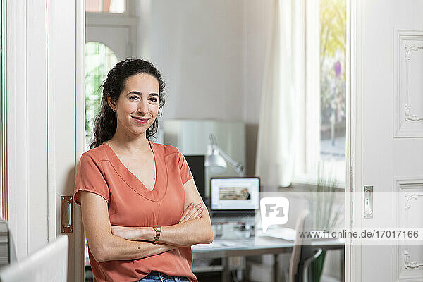 Happy businesswoman with arms crossed in office