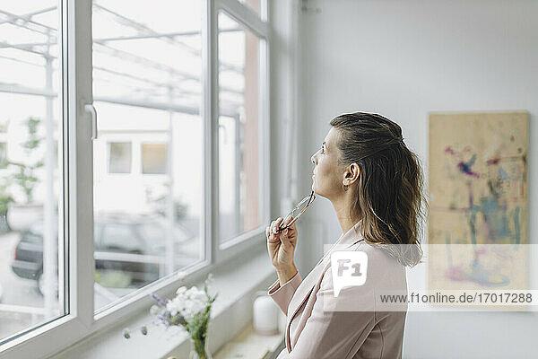 Businesswoman looking through windowin office