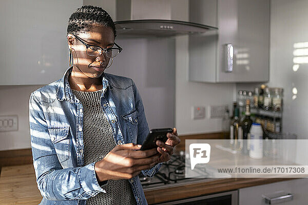 Woman looking at smart phone in kitchen