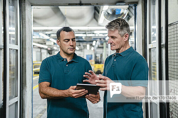 Male engineer discussing with colleague working in factory
