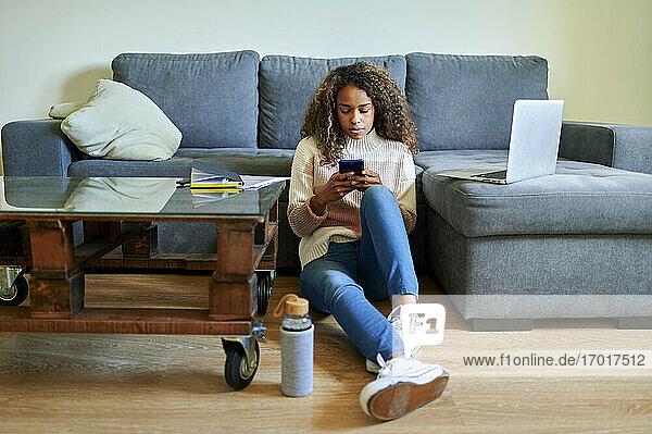 Junge Frau  die ein Mobiltelefon benutzt  während sie im Wohnzimmer zu Hause auf dem Boden sitzt Junge Frau, die ein Mobiltelefon benutzt, während sie im Wohnzimmer zu Hause auf dem Boden sitzt