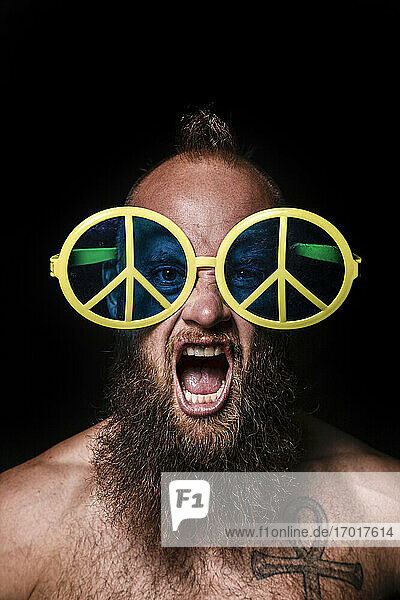 Male hipster shouting while wearing peace symbol sunglasses against black background