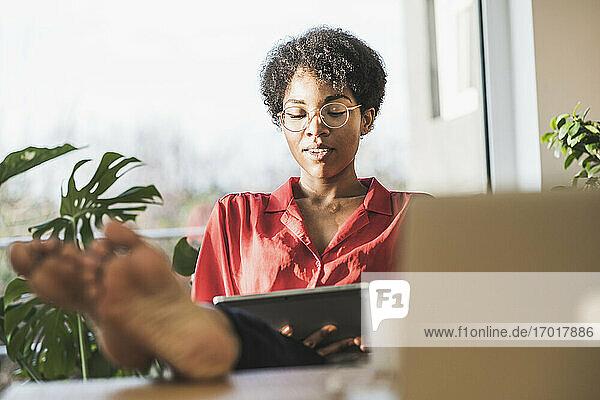 Frau mit nackten Füßen auf dem Schreibtisch mit digitalem Tablet Frau mit nackten Füßen auf dem Schreibtisch mit digitalem Tablet