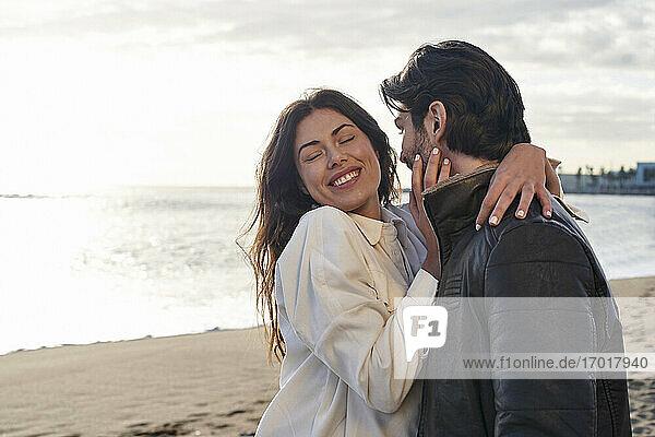 Glückliche Frau steht mit Arm um einen Mann am Strand