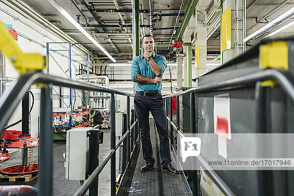 Male entrepreneur with hand on chin standing in industry