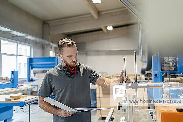 Porträt eines Schreiners  der mit einem Ringbuch in der Hand Maschinen in einer Produktionshalle inspiziert