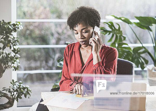 Frau  die am Schreibtisch mit einem Handy telefoniert und auf Dokumente schaut Frau, die am Schreibtisch mit einem Handy telefoniert und auf Dokumente schaut
