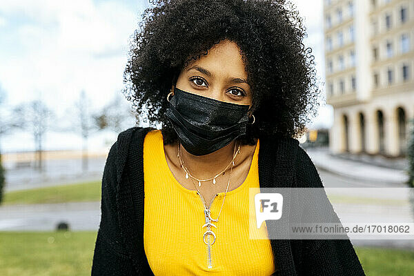 Close-up of young woman with afro hair wearing black face mask
