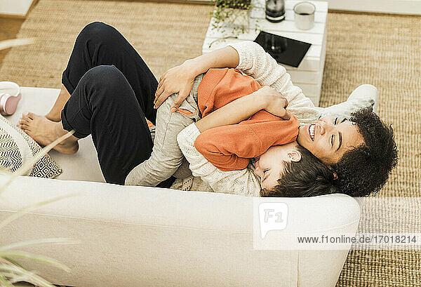 Lächelnde Mutter  die ihren Sohn umarmt  während sie zu Hause auf dem Sofa liegt Lächelnde Mutter, die ihren Sohn umarmt, während sie zu Hause auf dem Sofa liegt
