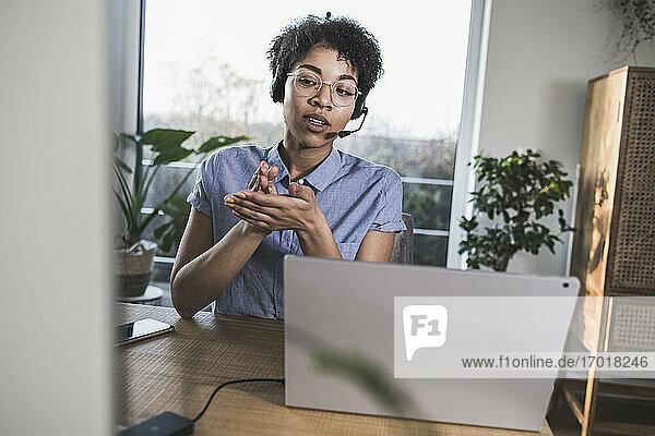 Frau mit Videokonferenz über Laptop zu Hause Frau mit Videokonferenz über Laptop zu Hause