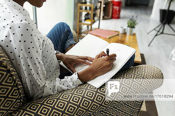 Lässige Geschäftsfrau  die in einem Sessel sitzt und in ihr Tagebuch schreibt Lässige Geschäftsfrau, die in einem Sessel sitzt und in ihr Tagebuch schreibt