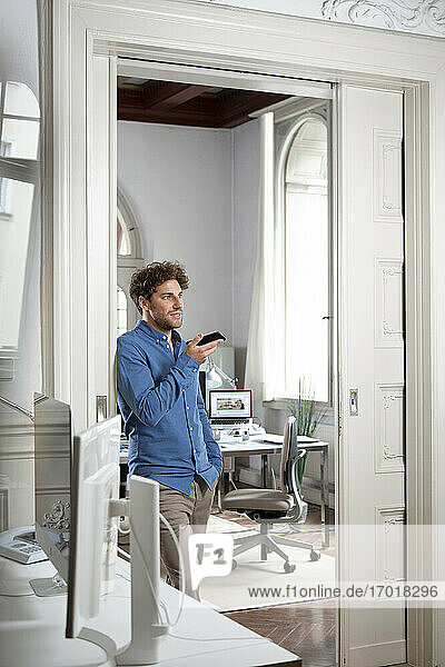 Male entrepreneur sending voicemail through mobile phone in office