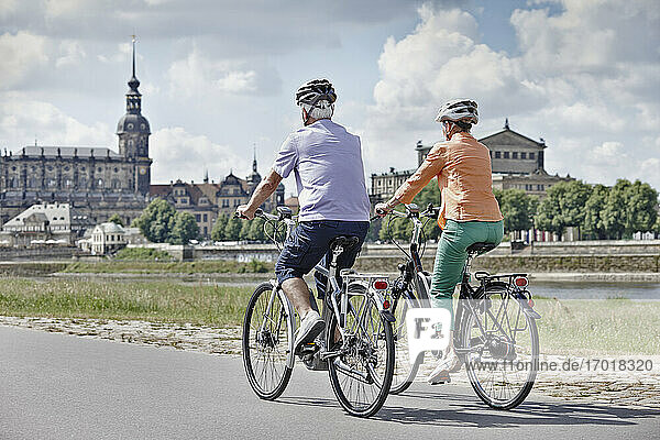 Tourist couple riding electric bicycle at Semper Opera House  Dresden  Germany