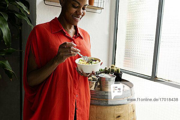 Frau steht zu Hause und isst eine Schüssel Salat Frau steht zu Hause und isst eine Schüssel Salat