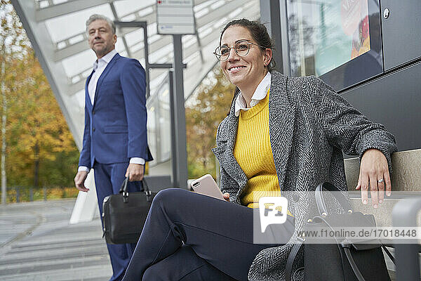 Smiling businesswoman sitting on bench while businessman waiting at bus stop