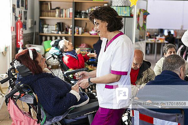 Pflegerin trägt Nagellack auf eine behinderte Frau im Rehabilitationszentrum auf