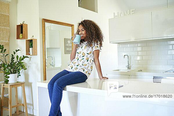 Glückliche afro-junge Frau  die Kaffee trinkt  während sie zu Hause auf dem Küchentisch sitzt Glückliche afro-junge Frau, die Kaffee trinkt, während sie zu Hause auf dem Küchentisch sitzt