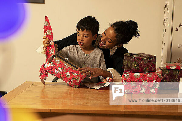 Cheerful mother with son unwrapping Christmas presents on table at home