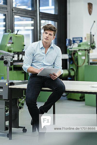 Männlicher Ingenieur mit Dokument  der wegschaut  während er auf einem Schreibtisch in der Industrie sitzt