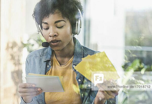 Frau mit Headset bei der Arbeit am Schreibtisch zu Hause Frau mit Headset bei der Arbeit am Schreibtisch zu Hause