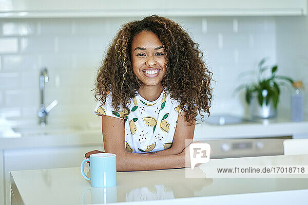 Lächelnde junge Afro-Frau mit Kaffeetasse  die sich in der Küche an den Tresen lehnt Lächelnde junge Afro-Frau mit Kaffeetasse, die sich in der Küche an den Tresen lehnt