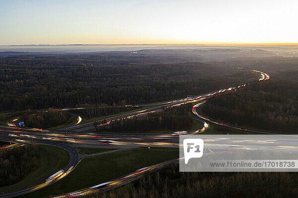 Germany  Baden-Wurttemberg  Stuttgart  Aerial view of vehicle light trails on Bundesautobahn 8 at sunset