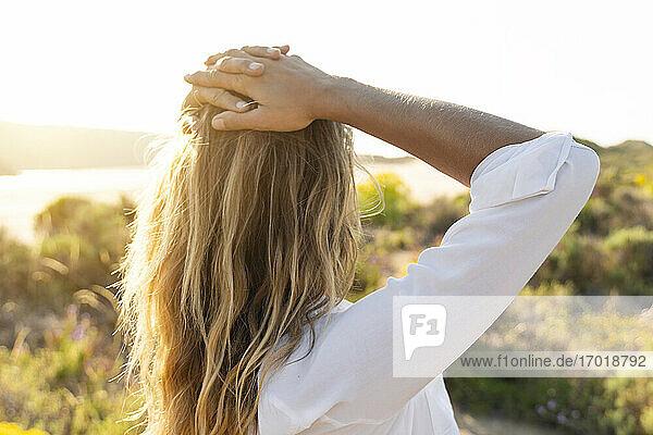 Frau  die am Strand stehend die Aussicht betrachtet Frau, die am Strand stehend die Aussicht betrachtet