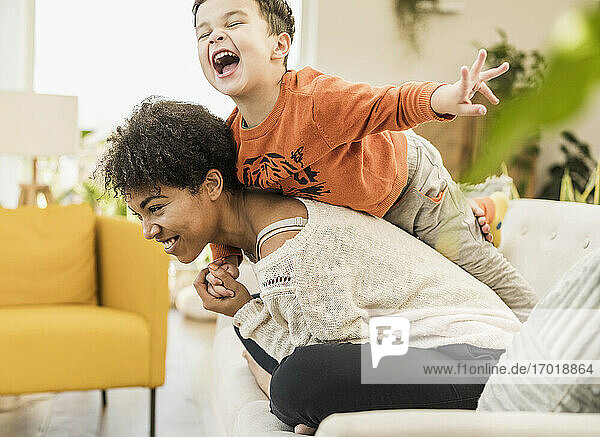 Glücklicher Sohn  der beim Spielen zu Hause huckepack auf seiner Mutter sitzt Glücklicher Sohn, der beim Spielen zu Hause huckepack auf seiner Mutter sitzt